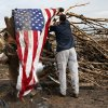 A man who asked not to be identified hangs an American flag on what is left of a tree in a neighborhood north of SW 149th between Western and Santa Fe on Tuesday, May 21, 2013, after a tornado struck south Oklahoma City and Moore, Okla., on Monday. Photo by Nate Billings, The Oklahoman