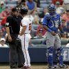 Atlanta Braves\' Dan Uggla, second from left, argues with umpire Doug Eddings, left, after striking out in the seventh inning of a baseball game as Kansas City Royals catcher Salvador Perez, right, looks on, Wednesday, April 17, 2013, in Atlanta. The Royals won 1-0. (AP Photo/David Goldman)