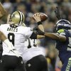 Photo - Seattle Seahawks defensive end Cliff Avril, right, causes New Orleans Saints quarterback Drew Brees (9) to fumble in the first half of an NFL football game, Monday, Dec. 2, 2013, in Seattle. Seahawks defensive end Michael Bennett recovered the fumble and ran for a touchdown. (AP Photo/Elaine Thompson)