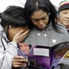 Danyia Bell, left 16, and Artureana Terrell , 16, react as they read a program for the funeral of Hadiya Pendleton outside the Greater Harvest Missionary Baptist Church after the funeral service of Hadiya Pendleton Saturday, Feb. 9, 2013, in Chicago. Hundreds of mourners and dignitaries including first lady Michelle Obama packed the funeral service Saturday for a Chicago teen whose killing catapulted her into the nation\'s debate over gun violence. (AP Photo/Nam Y. Huh)