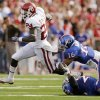 Photo - OU's Dejuan Miller (24) breaks away from KU defenders Chris Harris (16) and Darrell Stuckey (25) after a reception during the first half of the college football game between the University of Oklahoma Sooners (OU) and the University of Kansas Jayhawks (KU) on Saturday, Oct. 24, 2009, in Lawrence, Kan. OU won, 35-13. Photo by Nate Billings, The Oklahoman