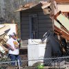 A man pauses during work to remove possessions from a tornado-damaged home in Century, Fla., Tuesday, Feb. 16, 2016. (AP Photo/Michael Snyder)