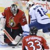 Photo - Ottawa Senators goalie Ben Bishop, left, stops a shot from Toronto Maple Leafs' Clarke MacArthur during the first period of an NHL hockey game in Ottawa, Ontario, on Saturday, Feb. 23, 2013. (AP Photo/The Canadian Press, Sean Kilpatrick)