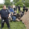 Protesters sit on a tent after it was torn down by police in a grassy area near the B-Line Trail, Tuesday, May 1, 2012 in Bloomington, Ind. The protesters claimed they set up the sent to have a free market as part of May Day activities. (AP Photo/Bloomington Herald-Times, Jeremy Hogan)