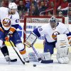 Photo - New York Islanders defenseman Andrew MacDonald (47) clears the puck as goalie Evgeni Nabokov (20), from Russia, watches in the first period of an NHL hockey game against the Washington Capitals, Tuesday, Feb. 4, 2014, in Washington. (AP Photo/Alex Brandon)