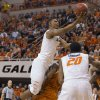 Oklahoma State forward Michael Cobbins, right, watches as Le\'Bryan Nash, left, takes a shot while being fouled by Texas guard Julien Lewis during the second half of an NCAA college basketball game in Stillwater, Okla., Saturday, March 2, 2013. Nash scored 16 points Oklahoma State\'s 78-65 win. (AP Photo/Brody Schmidt)