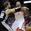 Photo - San Antonio Spurs' Tiago Splitter (22) knocks the ball away from Houston Rockets' Greg Smith (4) in the first half of an NBA basketball game, Monday, Dec. 10, 2012, in Houston. (AP Photo/Pat Sullivan)