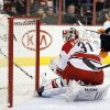 Photo - Carolina Hurricanes goalie Anton Khudobin, front, looks back at the puck in the net put there by Philadelphia Flyers' Claude Giroux, rear, during the second period of an NHL hockey game, Wednesday, Jan. 22, 2014, in Philadelphia. (AP Photo/Tom Mihalek)