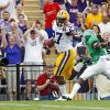 Photo -   LSU running back Kenny Hilliard (27) stiff arms North Texas defensive back Marcus Trice (8) on his way to scoring a touchdown during the first half of an NCAA college football game in Baton Rouge, La., Saturday, Sept. 1, 2012. (AP Photo/Bill Haber)