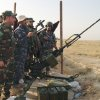 In this Friday, July 4, 2014 photo, Iraqi lawmaker Hakim al-Zamili, far left showing his face, visits fighters with