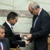 Greece\'s Finance Minister Yannis Stournaras, left, gives a disc containing the new draft state budget for 2013 to Parliament speaker Evangelos Meimarakis, right, at the Greek parliament in Athens, Wednesday, Oct. 31, 2012. Greek lawmakers are to vote Wednesday on a privatization bill that will be the first major test for the country\'s troubled governing coalition, while journalists have walked off the job at the start of rolling 24-hour strikes to protest austerity plans that will affect their healthcare funds. (AP Photo/Thanassis Stavrakis)