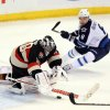 Ottawa Senators goaltender Ben Bishop (30) dives for a loose puck as Winnipeg Jets Alexander Burmistroc(8) looks on during second period NHL hockey action Saturday Feb. 9, 2013 in Ottawa. (AP Photo/The Canadian Press, Fred Chartrand)