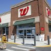 In this Wednesday, May 14, 2014 photo, a customer walks toward an entrance to a Walgreens store, in Boston. Walgreen plans to keep its roots firmly planted in the United States, saying Wednesday, Aug. 6, 2014 it will no longer pursue an overseas reorganization that would have trimmed the amount of U.S. taxes it pays. (AP Photo/Steven Senne)