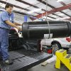 Photo -  Technician John Kline positions a new CNG tank Thursday during installation in a vehicle at Heartland Energy Options in Oklahoma City. Photo by Paul B. Southerland, The Oklahoman   PAUL B. SOUTHERLAND -
