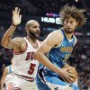 New Orleans Hornets center Robin Lopez (15) drives to the basket as Chicago Bulls forward Carlos Boozer (5) defends during the first half of an NBA basketball game in Chicago, Saturday, Nov. 3, 2012. (AP Photo/Nam Y. Huh)