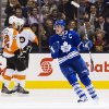 Toronto Maple Leafs\' Dion Phaneuf, right, celebrates his goal as Philadelphia Flyers\' Luke Schenn (22) and Wayne Simmonds skate by during the first period of their NHL hockey game, Monday, Feb. 11, 2013, in Toronto. (AP Photo/The Canadian Press, Chris Young)
