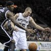 Photo - San Antonio Spurs' Nando De Colo, right, and Brooklyn Nets' Andray Blatche look to a loose ball during the first half of an NBA basketball game, Monday, Dec. 31, 2012, in San Antonio. (AP Photo/Darren Abate)