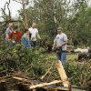 Dustin Moss, center, with chain saw, and others work to clear damaged trees in the Dripping Springs Estates Saturday, May 15, 2010. Saturday hundreds of volunteers went into areas that had been affected by last week\'s tornadoes to help clear debris. Photo by Doug Hoke, The Oklahoman.