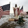 A religious statue with flags is see Tuesday, Feb. 5, 2013, near empty lots where homes destroyed by Superstorm Sandy were torn down in Union Beach, N.J. New Jersey Gov. Christie told a gathering in Union Beach Tuesday that the National Flood Insurance Program\'s handling of claims in New Jersey
