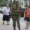 People walk past a pro-Russian fighter in the city of Donetsk, eastern Ukraine Friday, July 11, 2014. Ukrainian government troops have been fighting for more than three months against separatists in eastern Ukraine. In the last two weeks, however, they have cut the amount of territory held by the rebels in half and forced them out of their stronghold in the city of Slovyansk. The rebels have since regrouped in the eastern city of Donetsk and Ukraine has vowed to cordon the area. (AP Photo/Dmitry Lovetsky)