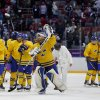 Photo - Sweden goaltender Henrik Lundqvist celebrates with teammates after Sweden beat Finland 2-1 in a men's semifinal ice hockey game at the 2014 Winter Olympics, Friday, Feb. 21, 2014, in Sochi, Russia. (AP Photo/Petr David Josek)