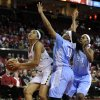 Maryland\'s Tianna Hawkins , left, looks to shoot as North Carolina\'s Brittany Roundtree, center, defends during the first half of an NCAA college basketball game on Thursday, Jan. 24, 2013, in College Park, Md. North Carolina\'s Xylina McDaniel, right, watches the play. (AP Photo/Gail Burton).
