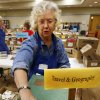 Photo -  Volunteer Jan Solberg sorts books for the Friends of the Norman Library's Better Books Sale that opens Friday and continues through Sunday. PHOTO BY STEVE SISNEY, THE OKLAHOMAN   STEVE SISNEY -