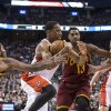Photo - Toronto Raptors' DeMar DeRozan, second from left, drives past Cleveland Cavaliers' Kyrie Irving, left, Tristan Thompson, second from right, and Tyler Zeller to score during first half of an NBA basketball game in Toronto, Friday, Feb. 21, 2014. (AP Photo/The Canadian Press, Chris Young)