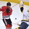 Chicago Blackhawks\' Jonathan Toews, left, tries to tip in the puck as Nashville Predators\' Pekka Rinne (35) blocks the shot during the second period of an NHL hockey game Monday, April 1, 2013, in Chicago. (AP Photo/Jim Prisching)
