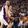 Photo -   Memphis Grizzlies guard Mike Conley, right, drives to the basket around Phoenix Suns center Marcin Gortat, left, of Poland, and Steve Nash, center, in the first quarter of an NBA basketball game Saturday, March 10, 20112, in Phoenix.(AP Photo/Paul Connors)