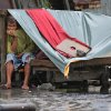 A Filipino man sits inside his makeshift home as strong winds and rains caused by Typhoon Koppu hits the coastal town of Navotas, north of Manila, Philippines on Sunday, Oct. 18, 2015. Slow-moving Typhoon Koppu blew ashore with fierce wind in the northeastern Philippines early Sunday, toppling trees and knocking out power and communications. (AP Photo/Aaron Favila)