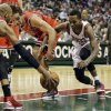 Milwaukee Bucks\' Brandon Jennings, right, and Chicago Bulls\' Joakim Noah (13) reach for a loose ball during the second half of an NBA basketball game Wednesday, Jan. 30, 2013, in Milwaukee. (AP Photo/Jeffrey Phelps)