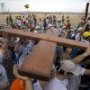 Photo - A wooden cross, symbol of the World Youth Day given to young people of the church in 1983 by Pope John Paul II,  is carried along Copacabana beach by pilgrims in Rio de Janeiro, Brazil, Sunday July 21, 2013. Pope Francis, the 76-year-old Argentine who became the church's first pontiff from the Americas in March, will return Monday to the embrace of Latin America to preside over the Roman Catholic Church's World Youth Day festival. (AP Photo/Victor R. Caivano)