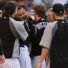Photo - Colorado Rockies' Drew Stubbs, center back, is surrounded by teammates as Stubbs crosses home plate after hitting a three-run, walkoff home run against the Cincinnati Reds in the ninth inning in a baseball game in Denver on Sunday, Aug. 17, 2014. The Rockies won 10-9. (AP Photo/David Zalubowski)