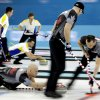 Photo - Canada's Ryan Fry delivers the rock while E.J. Harnden, right, and Ryan Harnden, center, sweeps the ice during the men's curling competition against Denmark at the 2014 Winter Olympics, Thursday, Feb. 13, 2014, in Sochi, Russia. (AP Photo/Wong Maye-E)