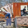 People remove possessions from a tornado-damaged home in Century, Fla., Tuesday, Feb. 16, 2016. (AP Photo/Michael Snyder)