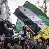 In this Friday, Nov. 30, 2012 photo, Syrians chant slogans and wave revolutionary flags during a demonstration after Friday prayers in the Bustan Al-Qasr district of Aleppo, Syria. After months of fighting, thousands of residents have returned to the city as they attempt to return to their daily lives while heavy fighting is still taking place along the front lines in the city. Public demonstrations have unfolded after several weeks of silence as residents demand an end to the violence in Aleppo. (AP Photo/Narciso Contreras)