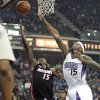 Photo - Miami Heat guard Mario Chalmers, left, drives to the basket against Sacramento Kings center DeMarcus Cousins, right,  during the first quarter of an NBA basketball game in Sacramento, Calif., Saturday, Jan. 12, 2013. (AP Photo/Rich Pedroncelli)