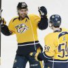 Photo - Nashville Predators defenseman Roman Josi (59), of Switzerland, is congratulated by Mike Fisher (12) after Josi scored against the San Jose Sharks in the second period of an NHL hockey game Tuesday, Jan. 7, 2014, in Nashville, Tenn. (AP Photo/Mark Humphrey)