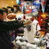 Photo - In this Jan. 29, 2008 file photo, Mike San Miguel, of La Verne, Calif., checks out the Super Bowl merchandise in the Arizona Highways retail store at Phoenix Sky Harbor International Airport before catching a flight.  Broadway producers, merchants and restaurateurs may not see the profits they hope will come with the Super Bowl visiting New York as fans will more likely spend their money on NFL branded merchandise and events.  (AP Photo/Ross D. Franklin, File)
