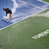 A worker dries the court during a rain delay at the Rogers Cup men\'s tennis tournament in Toronto on Thursday, Aug. 9, 2012. (AP Photo/The Canadian Press, Aaron Vincent Elkaim)