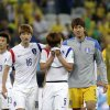 Photo - South Korea's Kim Young-gwon, center, is comforted by his teammates Ki Sung-yueng, left, and goalkeeper Lee Bum-young, right, after the group H World Cup soccer match between South Korea and Belgium at the Itaquerao Stadium in Sao Paulo, Brazil, Thursday, June 26, 2014. Belgium beat South Korea 1-0 to top Group H of the World Cup. South Korea was eliminated.  (AP Photo/Felipe Dana)