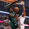 Photo - Boston Celtics forward Jeff Green, center, goes to the basket against Chicago Bulls guard Jimmy Butler, left, and center Joakim Noah, right, during the first half of an NBA basketball game in Chicago, Monday, March 31, 2014. (AP Photo/Kamil Krzaczynski)