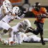 Oklahoma State\'s Josh Stewart (5) tries to get away from Texas\' Kenny Vaccaro (4), Mykkele Thompson (2), and Jackson Jeffcoat (44) during a college football game between Oklahoma State University (OSU) and the University of Texas (UT) at Boone Pickens Stadium in Stillwater, Okla., Saturday, Sept. 29, 2012. Oklahoma State lost 41-36. Oklahoma State lost 41-36. Photo by Bryan Terry, The Oklahoman