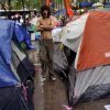 Mike Esperson, 22, from Queens, N.Y., who woke up to find himself soaked from rain, walks shirtless in the encampment of Occupy Wall Street protesters at Zuccotti Park on Thursday, Oct. 27, 2011 in New York. Esperson received free clothing at the camp\'s comfort station and says he is committed to the movement.