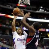 Photo - Los Angeles Clippers guard Chris Paul (3) shoots over Atlanta Hawks forward Paul Millsap (4) in the first half of an NBA basketball game, Saturday, March 8, 2014, in Los Angeles. (AP Photo/Gus Ruelas)