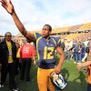 West Virginia quarterback Geno Smith gestures to fans after their NCAA college football game against Baylor in Morgantown, W.Va., Saturday, Sept. 29, 2012. Smith threw for 656 yards and tied a Big 12 record with eight touchdown passes to lead No. 9 West Virginia to a 70-63 win over No. 25 Baylor . (AP Photo/Christopher Jackson)