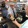 In this Nov. 29, 2012 file photo, television cameras rolling, as store manager Bob Chebat, middle, hands over Wes Prinzen\'s, right, modest $4 winnings, at a 4 Sons Food Store where one of the winning tickets in the $579.9 million Powerball jackpot was purchased in Fountain Hills, Ariz. When two winning tickets for a record Powerball jackpot were claimed last month, the world focused on the winners. One, from Missouri, showed up at the newsconference, while the other, in Arizona, chose to remain anonymous. Releasing information on the lottery winners reflects a broader debate playing out in state Legislatures and lottery offices nationwide: Should the winners' names be made public?(AP Photo/Ross D. Franklin, file)