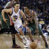 Photo - Milwaukee Bucks' Brandon Jennings, right, drives the ball past Golden State Warriors' Stephen Curry (30) during the first half of an NBA basketball game Saturday, March 9, 2013, in Oakland, Calif. (AP Photo/Ben Margot)