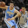 Denver Nuggets\' Danilo Gallinari, left, of Italy, grabs a loose ball behind San Antonio Spurs\' Danny Green during the first half of an NBA basketball game, Saturday, Nov. 17, 2012, in San Antonio. (AP Photo/Darren Abate)